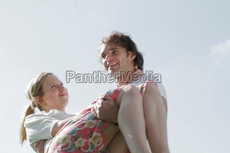 smiling man carrying girlfriend