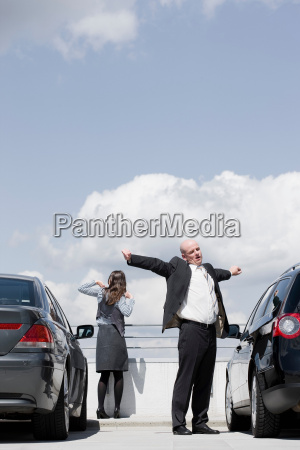 man and woman stretching between cars