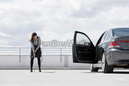 woman playing golf near car