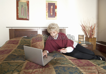 older woman using laptop on bed