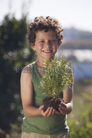young boy holding small plant