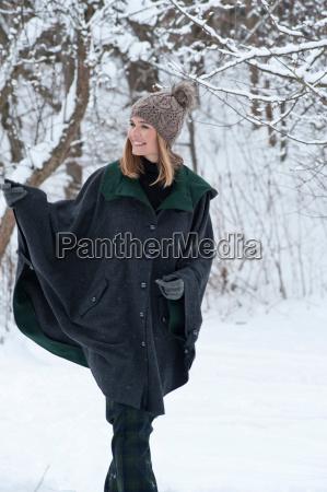 woman in heavy cape walking in