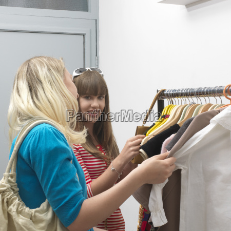 2 young women standing at clothes