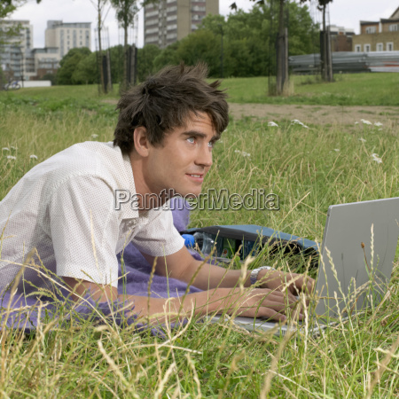 young man with laptop lying in