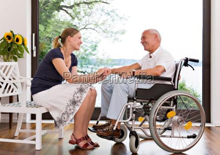 woman holding senior mans hand