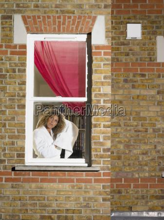 woman drying her hair in window