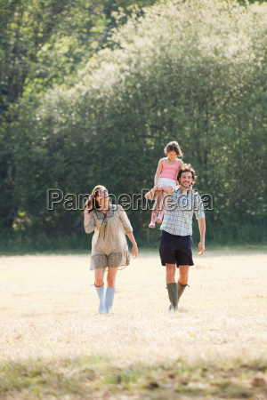 family walking through country field