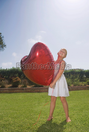 young girl holding big red heart