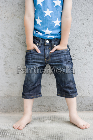 young boy standing at wall