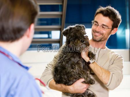 man holding dog at vet