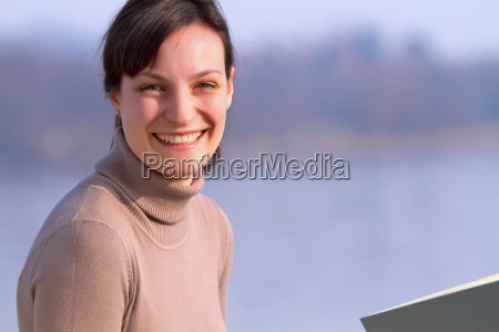woman sitting with book outdoors