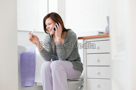 woman on cell phone with pregnancy