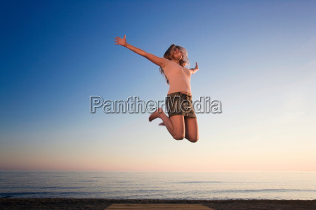 woman on beach jumping for joy