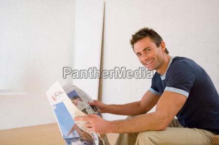 smiling man reading newspaper