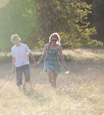 teenage couple walking together in field