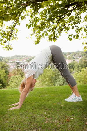 mature woman doing yoga stretch in