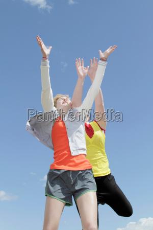 girls jumping for joy against blue