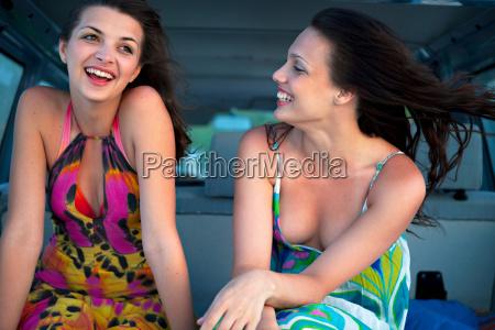 women in back of car