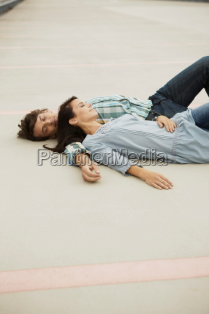 couple sleeping on park deck