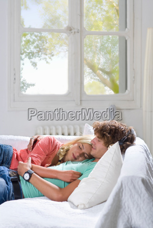 young couple sleep on couch at