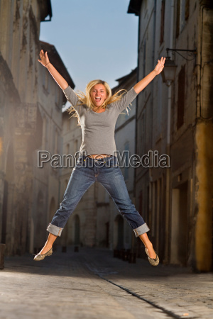 young woman jumps in street at