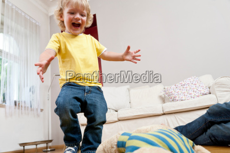 boy jumping in living room