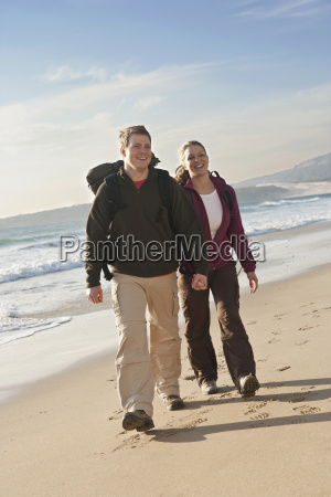 young backpackers holding hands at beach