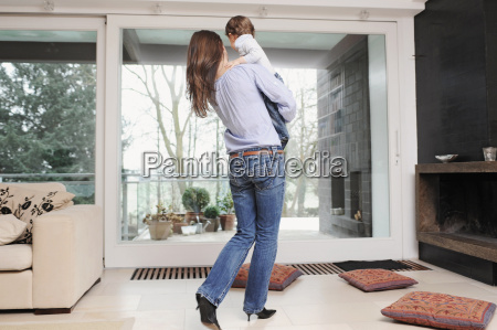 mother holding son in living room