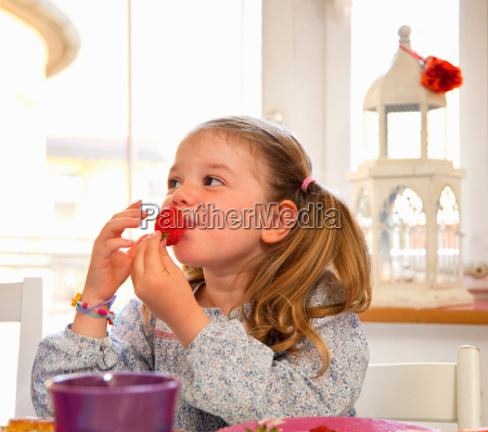 girl eating a strawberry at table