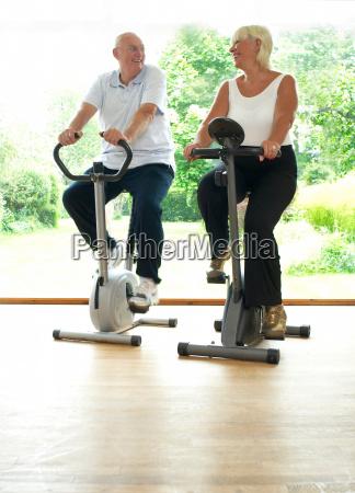 older couple riding stationery bikes