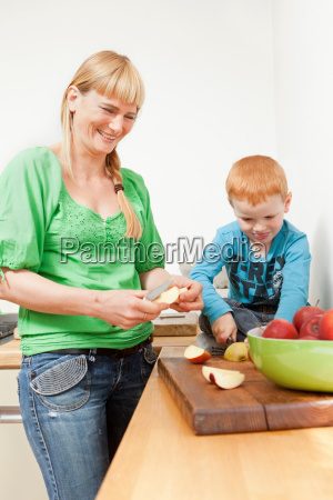 mother and son slicing apples together