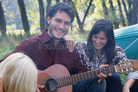man at campsite playing guitar