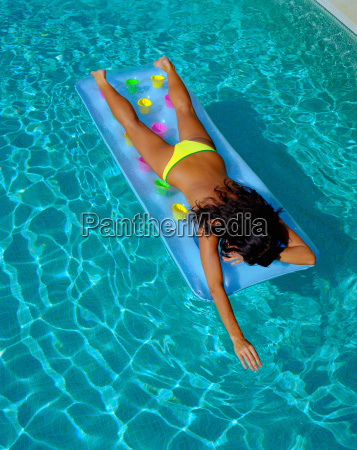 woman floating in a pool on