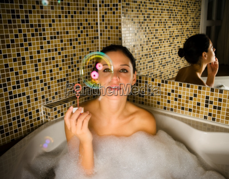 woman in bath looking at bubble