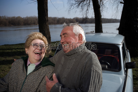 senior couple laughing by car