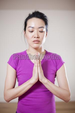 close up of woman meditating indoors