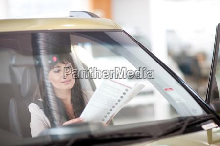 mid adult woman reading car brochure
