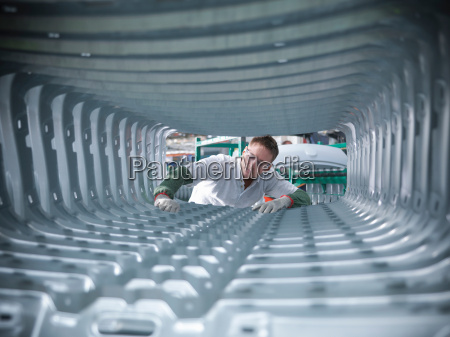 worker inspecting car body pressings in