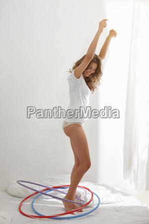 smiling woman hula hooping indoors