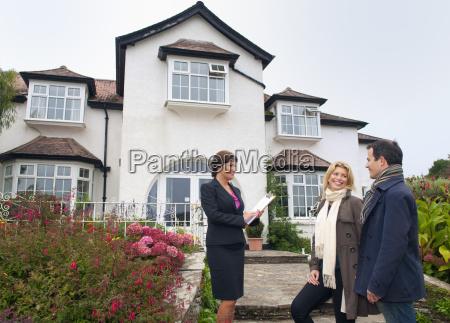 mittleres erwachsenes paar und immobilienmakler ausserhalb