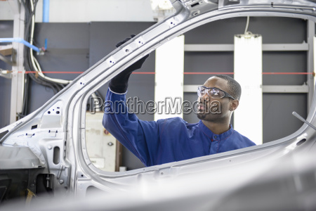 worker inspecting paint finish in car