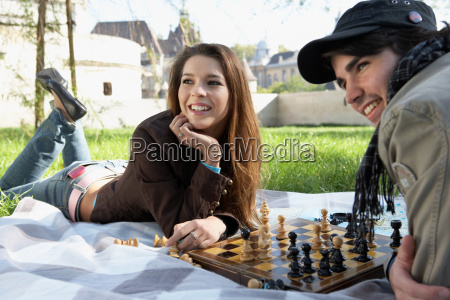 couple playing chess in a park