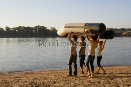 four friends carrying a raft on