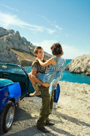 man holding woman aloft by car