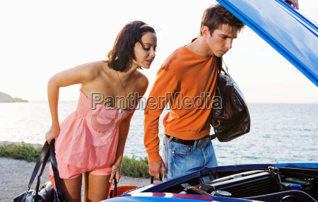 man and woman looking under car