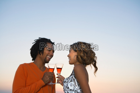 young couple drinking wine by sunset