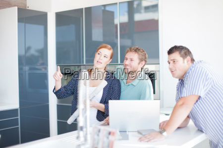 young couple with salesman in kitchen