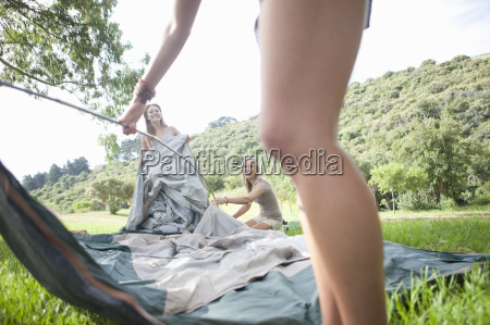 three friends constructing tent whilst camping