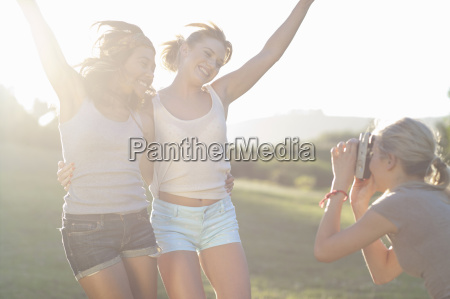 young female friends posing for photographs