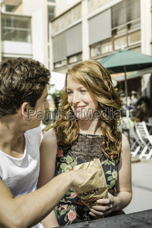 young couple sharing bag of food